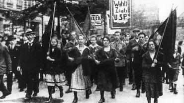 Die Aufnahme aus dem Jahr 1919 zeigt einen Demonstrationszug mit Frauen an der Spitze der die Unabhängige Sozialdemokratische Partei Deutschlands (USPD) und deren Kandidatin Luise Zietz unterstützt. Während des Hamburger Hafenarbeiterstreiks von 1896 organisierte sie den Widerstand der Frauen. 1917 gehörte Luise Zietz zu den Gründungsmitgliedern der USPD, sie gehörte 1919/20 der Weimarer Nationalversammlung an und war anschließend bis zu ihrem Tode Reichstagsabgeordnete.